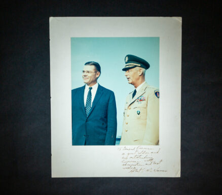 Photograph of Secretary of Defense Robert S. McNamara with Army General Paul L. Freeman, Jr., signed on the mount by McNamara with inscription.