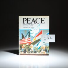 First edition of Peace, a photographic history of the Camp David Accords, with text by Anthony S. Pitch and a preface by Chaim Herzog. Signed by President Jimmy Carter on the half-title.